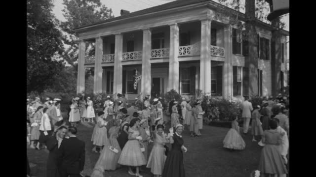 WS lawn party at antebellum mansion Arlington Antebellum Home and Gardens women in fancy dresses / Rosalind Russell sits with group of women in...