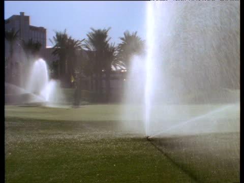 lawn sprinkler rotating over lush grass on sunny day sprays onto camera lens las vegas - sprinkler stock-videos und b-roll-filmmaterial