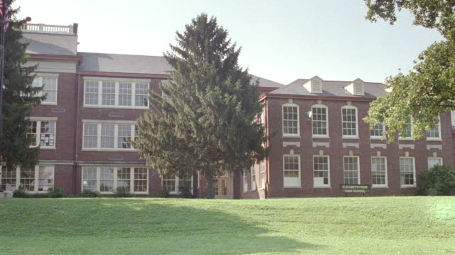 a lawn surrounds a three-story red brick school. - brick stock videos & royalty-free footage
