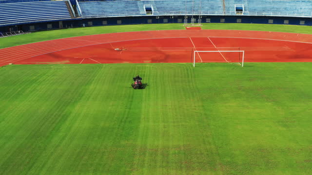 lawnmower cutting grass in public stadium in thailand - tractor stock videos & royalty-free footage