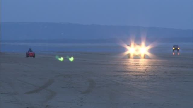 a lawnmower drives across a desert at dusk. - test drive stock videos & royalty-free footage