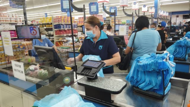 lay guzman stands behind a partial protective plastic screen and wears a mask and gloves as she works as a cashier at the presidente supermarket on... - checkout stock videos & royalty-free footage