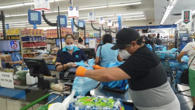 vidéos et rushes de lay guzman stands behind a partial protective plastic screen and wears a mask and gloves as she works as a cashier at the presidente supermarket on... - denrée périssable