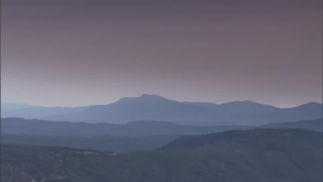 vidéos et rushes de a layer of fog lies near the base of a volcanic mountain. - horizon