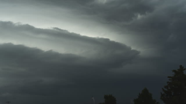 Layers of massed gray clouds blowing across the sky, time lapse