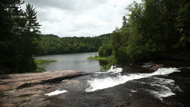 Layers of Waterfalls Flowing into Quiet Lake in Canadian Forest