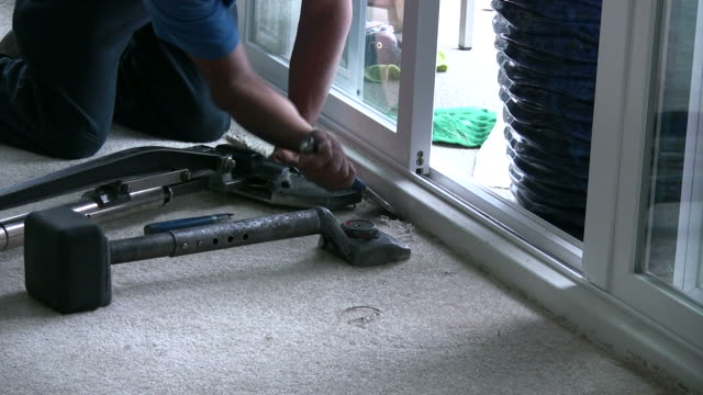 (hd1080i) laying carpet, using chisel to stretch rug into corner - installing stock videos & royalty-free footage
