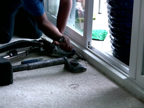 laying carpet, using chisel to stretch rug into corner - installing stock videos and b-roll footage