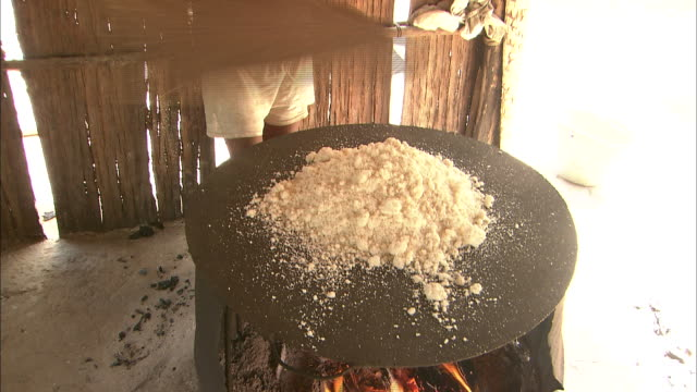 Laying Cassava (Yucca) Flour On A Hotplate In The Village Of Santa Marta, Colombia