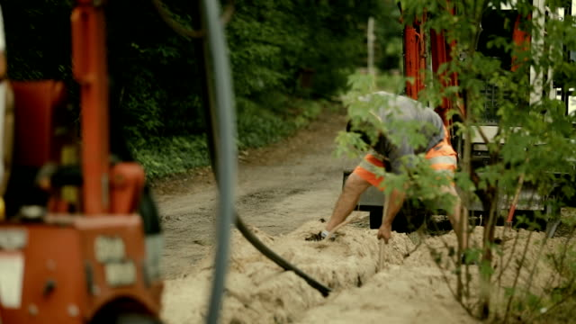 laying of a high-speed internet cable  - underground engineering - road construction stock videos and b-roll footage