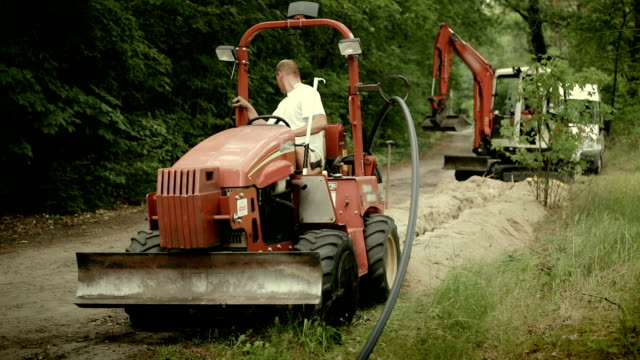 laying of a high-speed internet cable - underground engineering - traktor stock-videos und b-roll-filmmaterial
