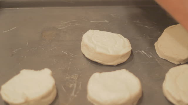 vídeos de stock, filmes e b-roll de laying prepared biscuit dough on a baking plate 2 - dedo humano