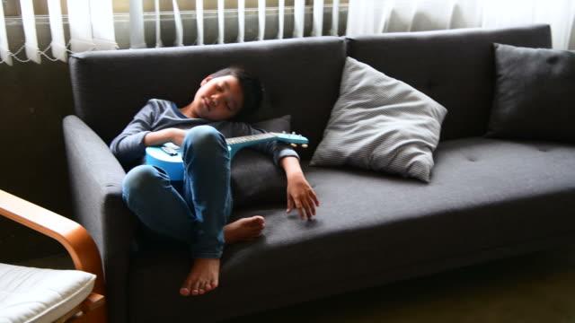 vídeos de stock, filmes e b-roll de menino preguiça deitado no sofá - esperar