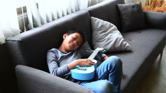 laziness boy lying down on sofa - un ragazzo adolescente video stock e b–roll