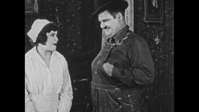 vídeos de stock e filmes b-roll de 1925 lazy boss (oliver hardy) flirts with attractive nurse as clumsy helper tries to decorate room single-handedly - 1925