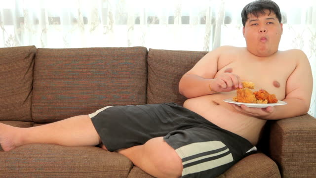 lazy overweight asian male with fast food and watching television - sofa stock videos & royalty-free footage