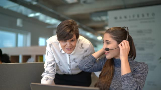 leader-geschäftsfrau unterstützt mitarbeiter mit headset bei der arbeit - headset stock-videos und b-roll-filmmaterial