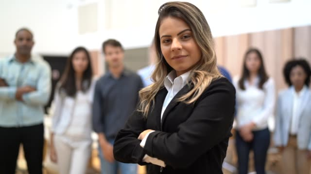 vídeos de stock, filmes e b-roll de empresária de líder com a equipe de negócios confiante no plano de fundo - mulher de negócios