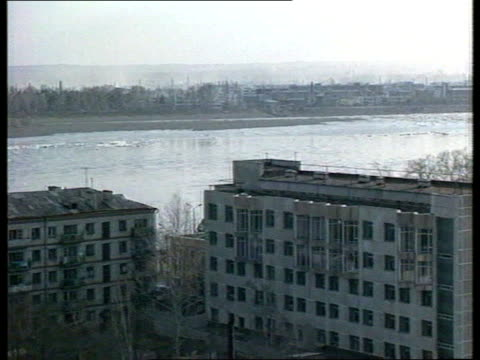 leaders meeting preparations; ussr , russia, blagoveshensk river amur dividing china & russia, zoom out to town buildings ice floes along as ships in... - zoom in点の映像素材/bロール