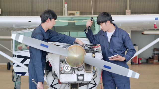 leadership asian teenage boy development engineer teaching engineering maintenance in hangar airplane.technology,science,stem,innovation,leadership,empowerment,expertise,mentorship concept.blue collar workers - engineer stock videos & royalty-free footage