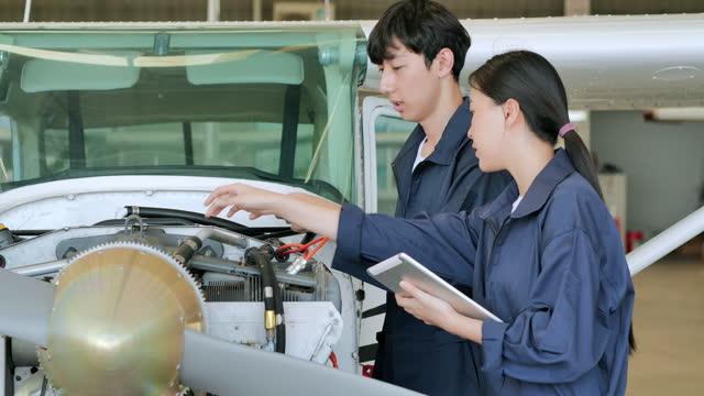 leadership asian teenage girl development engineer teaching engineering maintenance in hangar airplane.women in stem concept. - air vehicle stock videos & royalty-free footage
