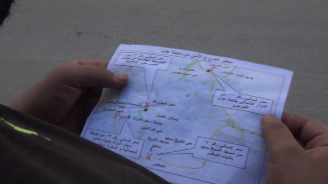 a leaflet dropped by syrian government forces in syria urging rebel groups to put down their arms and leave the city of aleppo - flyer leaflet stock videos and b-roll footage