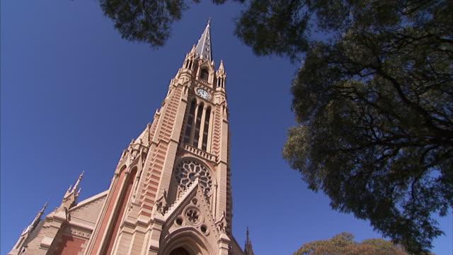 vídeos de stock e filmes b-roll de leafy branches frame the neo-gothic spires of a church in buenos aires. - argentina