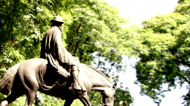 Leafy trees frame a statue of a man on horseback in Buenos Aires. Available in HD.