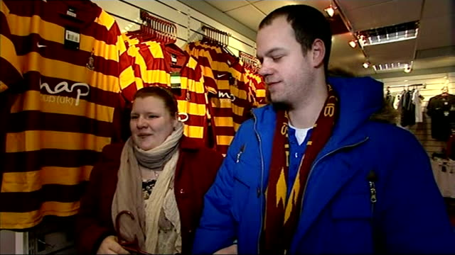 bradford city through to final chris kamara interview vox pops / fans looking at bradford city football shirts in club shop and man trying on shirt /... - top garment stock videos & royalty-free footage