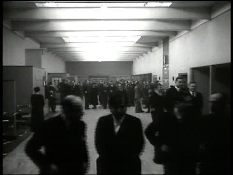 vídeos de stock e filmes b-roll de league of nations building int building w/ politicians walking together in lobby men standing bg - 1935