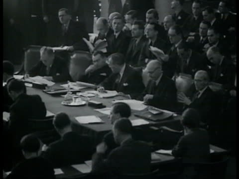 League of Nations in session w/ empty Germany chair British Sir Anthony Eden talking w/ Russian Maxim Litvinov French Foreign Minister Pierre Laval...