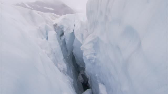 leaning walls of ice create a deep crevasse. - crevasse stock videos & royalty-free footage