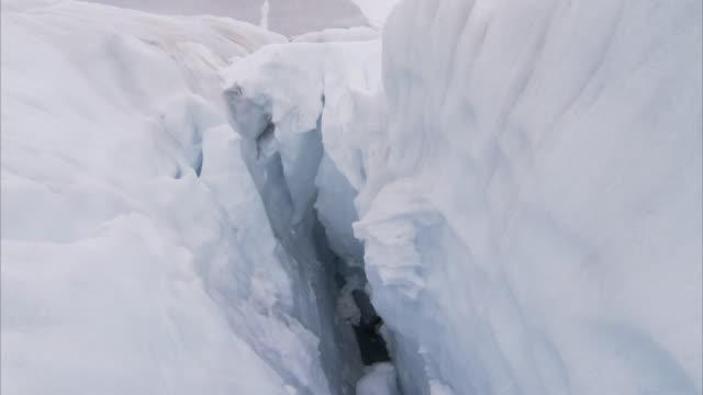 leaning walls of ice form a deep crevasse. - 割れ目点の映像素材/bロール