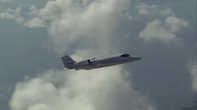 air to air ws learjet flying past clouds - air vehicle stock videos & royalty-free footage