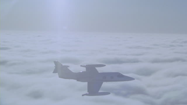 a learjet tilting left and right as it flies over clouds. - corporate jet stock videos & royalty-free footage
