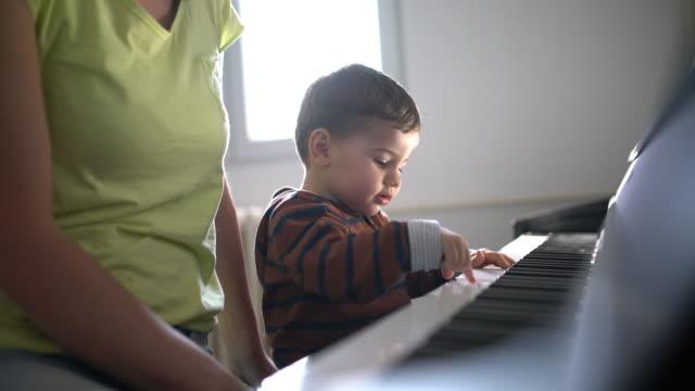 vídeos de stock e filmes b-roll de learning to play the piano - família monoparental