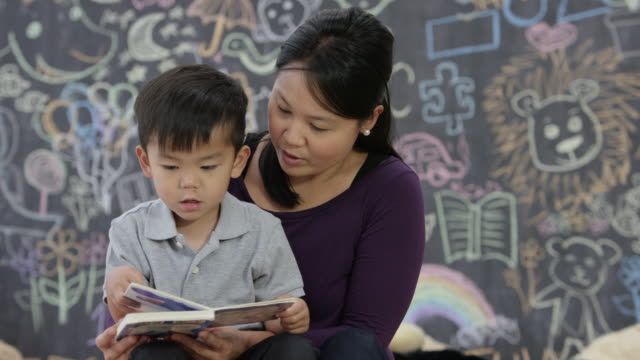 vídeos de stock, filmes e b-roll de aprendendo a leitura na creche - etnia oriental