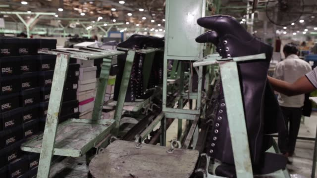 Leather boots hang on a rack while moving along a conveyor on the assembly line at a Virola Shoes Pvt manufacturing facility in Agra Uttar Pradesh...