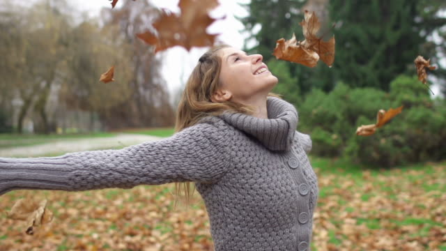 Leaves falling on girl while spinning and having fun