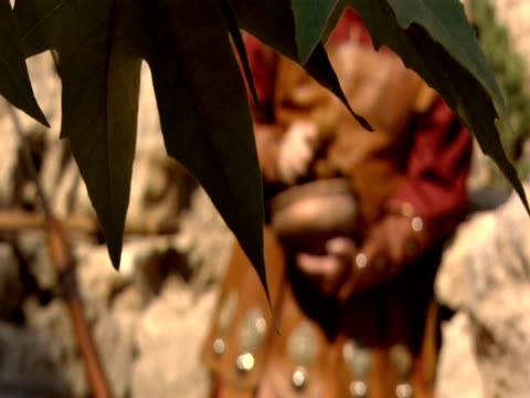 vídeos y material grabado en eventos de stock de leaves in foreground obscuring a soldier squeezing water from sponge in reenactment of the crucifixion of jesus - centurión