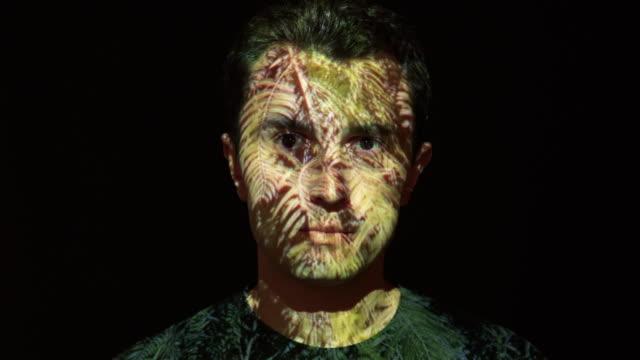 Blätter-Projektion auf das Gesicht des Mannes