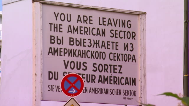 vídeos de stock, filmes e b-roll de ms leaving american area sign at checkpoint charlie, berlin wall crossing point between east germany and west germany during cold war / berlin, germany - east berlin