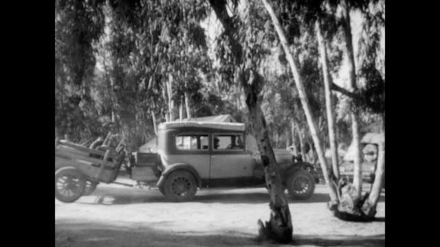 vidéos et rushes de leaving behind the dust bowl / line of cars heading west / okies travelling to california / women unloading back of truck men sitting dust bowl... - tempête de poussière