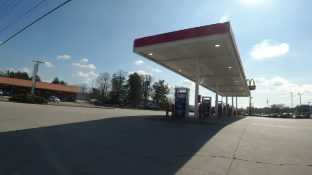 leaving exxon and mobil gas station in north georgia usa with mcdonald's sign in the background - exxon stock videos & royalty-free footage