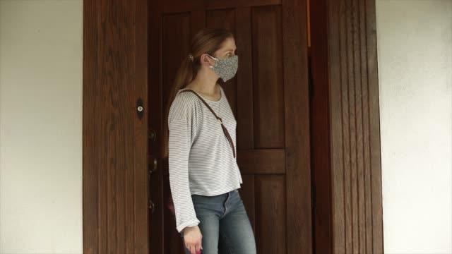 vídeos y material grabado en eventos de stock de leaving house front door wearing a mask - sale