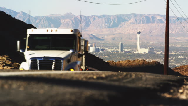 leaving las vegas: a semi truck drives away from las vegas on east lake mead blvd on highway 147 with with red rock canyon area appearing behind the las vegas skyline. - articulated lorry stock videos & royalty-free footage