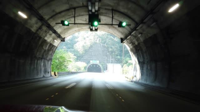 vídeos de stock, filmes e b-roll de saindo de um túnel e entrando em outro - ponto de vista de carro