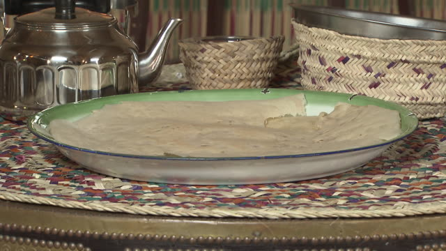 vídeos de stock e filmes b-roll de markook. view of a tray of uncooked unleavened flatbread with a tea kettle in the background. - agrafo