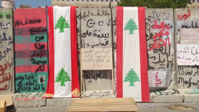 vídeos y material grabado en eventos de stock de lebanese protesters draw graffities on the concrete blast walls installed by the security forces in front of the governmental palace building in the... - pared de cemento