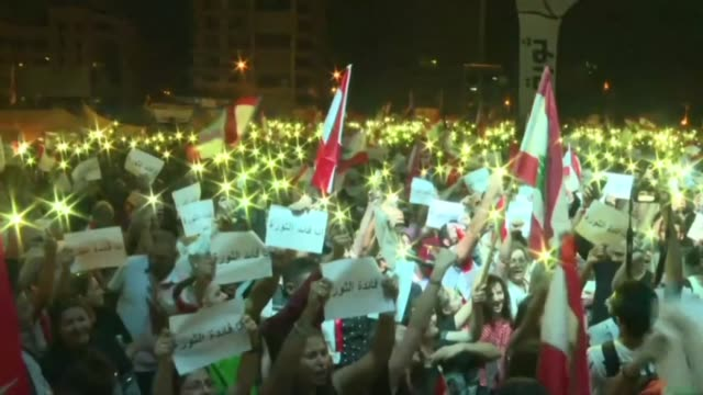 lebanese protesters gather in mass in beirut's martyrs square at dusk chanting revolution and waving national flags on the tenth consecutive day of... - revolution stock videos & royalty-free footage